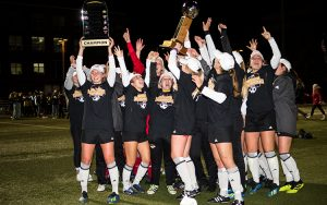 Players stand on the soccer field holding aloft two championship trophies.