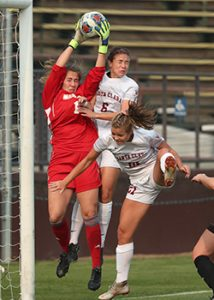 A goalkeeper jumps and catches the ball high above her head as two opponents try to head the ball.