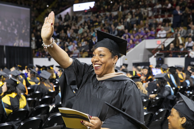 A woman waves.