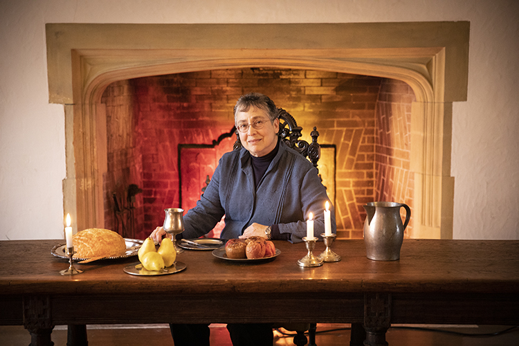 A woman sits at a table in front of a fireplace. The table holds food, candles and a water pitcher.