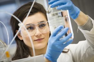 A woman wearing gloves and safety glasses lifts a beaker and looks at it.