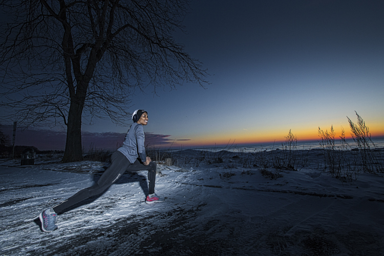Wilkistat Otieno stretching before a early morning run with a first crack of dawn sunrising the background