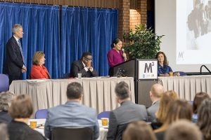 A woman speaks at a podium while others sit at a table flanking her.