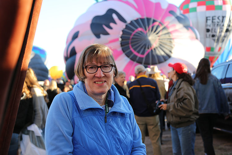 A woman stands in front of two hot-air balloons.