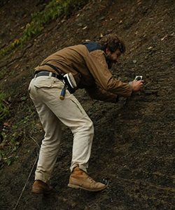 A man perches on a steep hill, examining the rock surface.