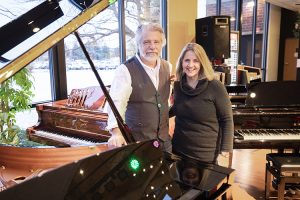 A man and woman stand near a grand piano.