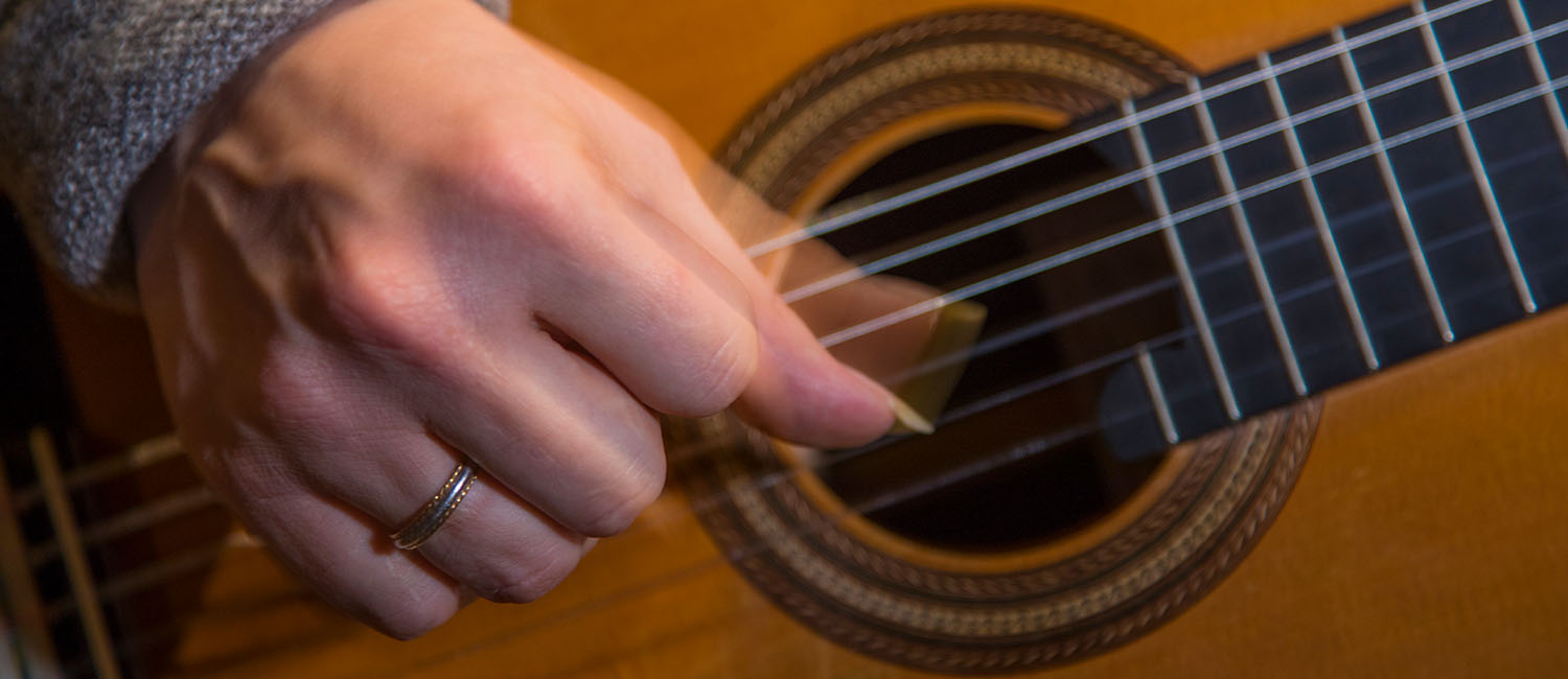 A hand strumming a guitar