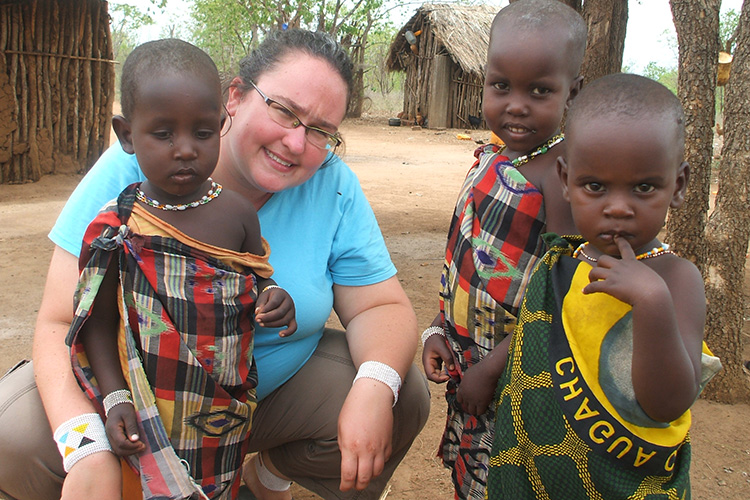 A woman poses with three small children in Tanzania.