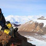 A woman sits atop a mountain.