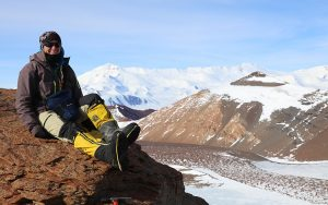 A woman sits atop a mountain.