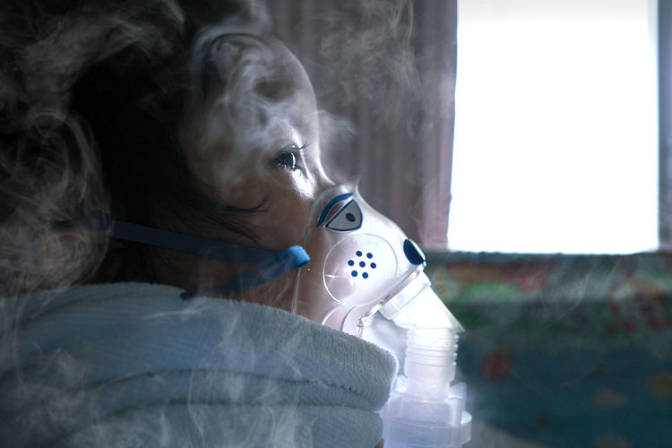 Image of a child wearing a mask to protect her from smoke