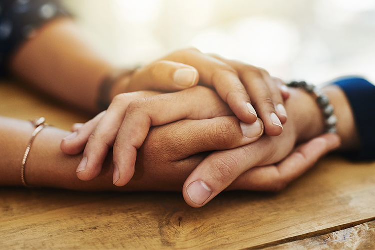 Image of two clasped hands, giving comfort