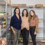 Three women stand among shelves of food.