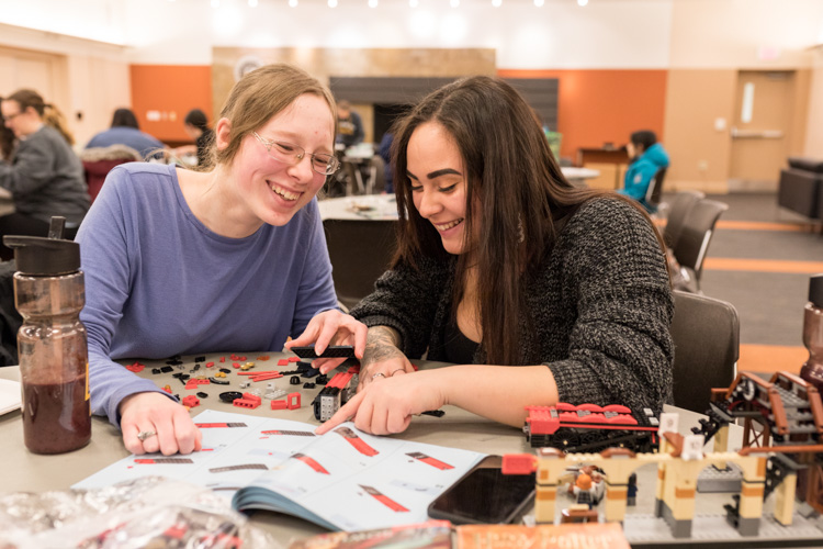 Two women sit at a table using Legos.