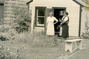 A black and white photo shows three women standing near a garden near a shed.