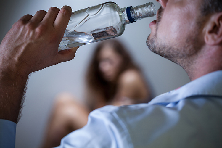 A man drinks from a bottle while a woman cowers.