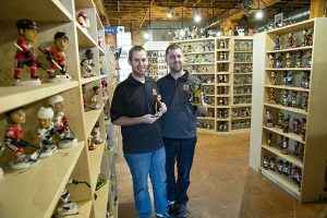 Two men stand in a room full of shelves filled with bobbleheads.