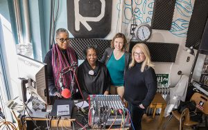 Four women pose for a photo behind a radio station desk.