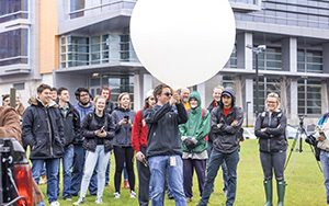 Several people stand outside watching a man holding a balloon aloft.