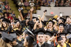 Students dressed in caps and gowns throw their arms in the air and smile.