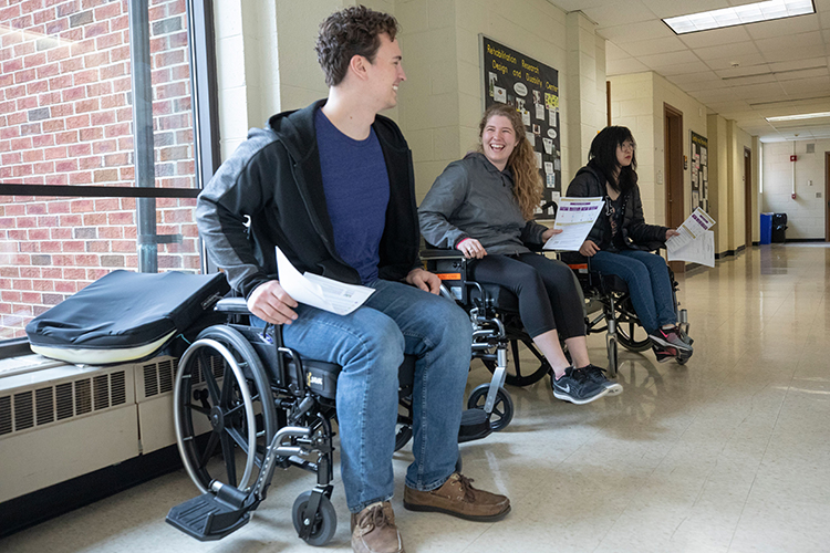 A man and two women sit in three different wheelchairs.