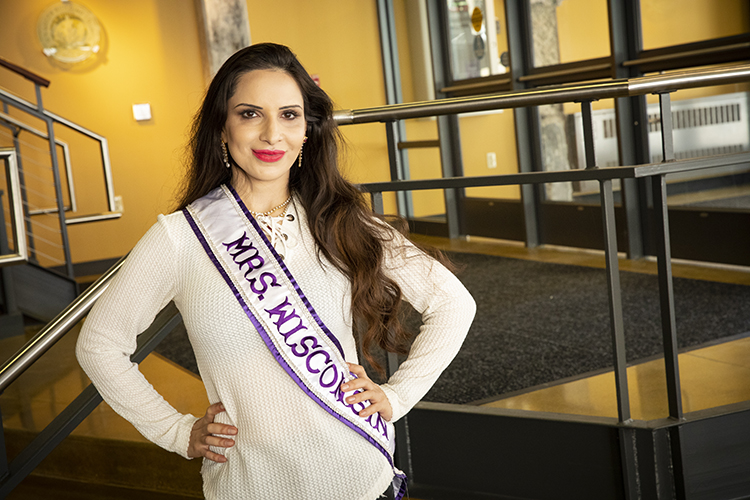 A woman wearing a Mrs. Wisconsin sash poses for a photo.