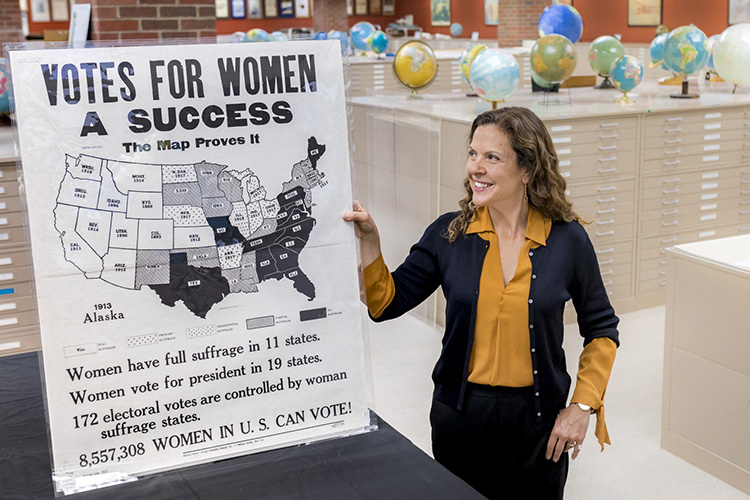 A woman stands with a poster.