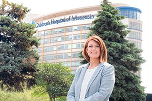 A woman stands in front of the Children's Hospital of Wisconsin.