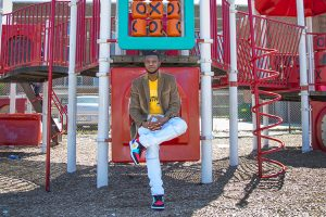 A man sits on some playground equipment.