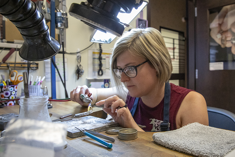 A woman sits at a workbench using a small torch.