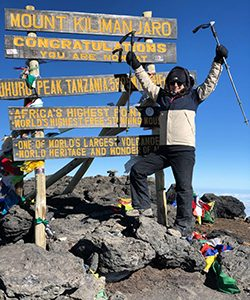 A woman lifts her arms in celebration atop Mount Kilimanjaro.