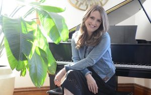 A woman poses in front of a piano.