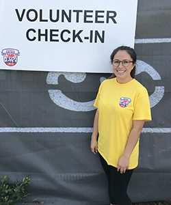 "A woman stands in front of a ""volunteer check-in"" sign."