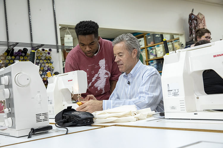 Mark Mone at sewing machine with student