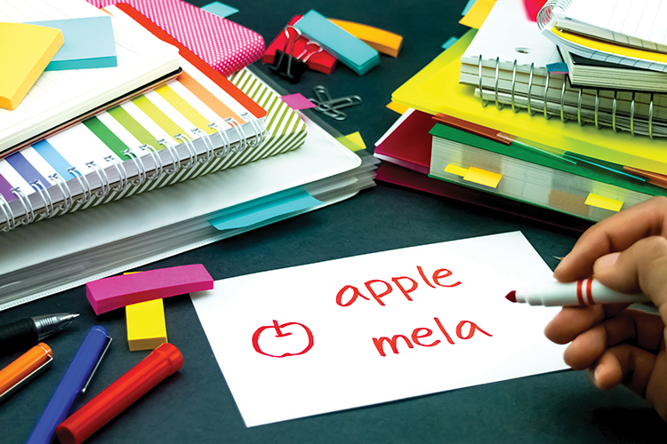 Books and other school supplies, with a hand writing 'apple mela' on a notecard