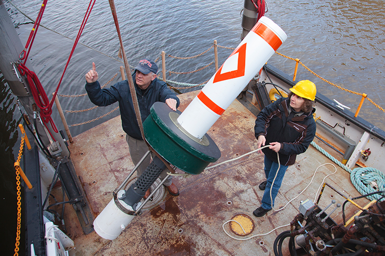 Two people on deck of boat using heavy machinery to lift object