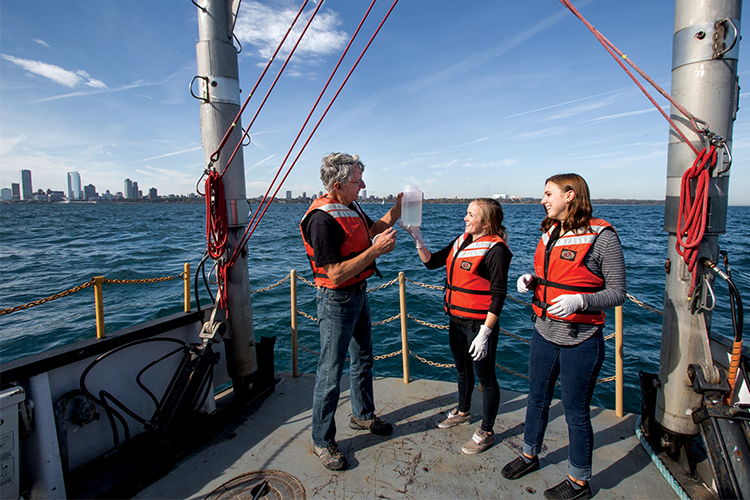Three people look at a water sample on deck of boat