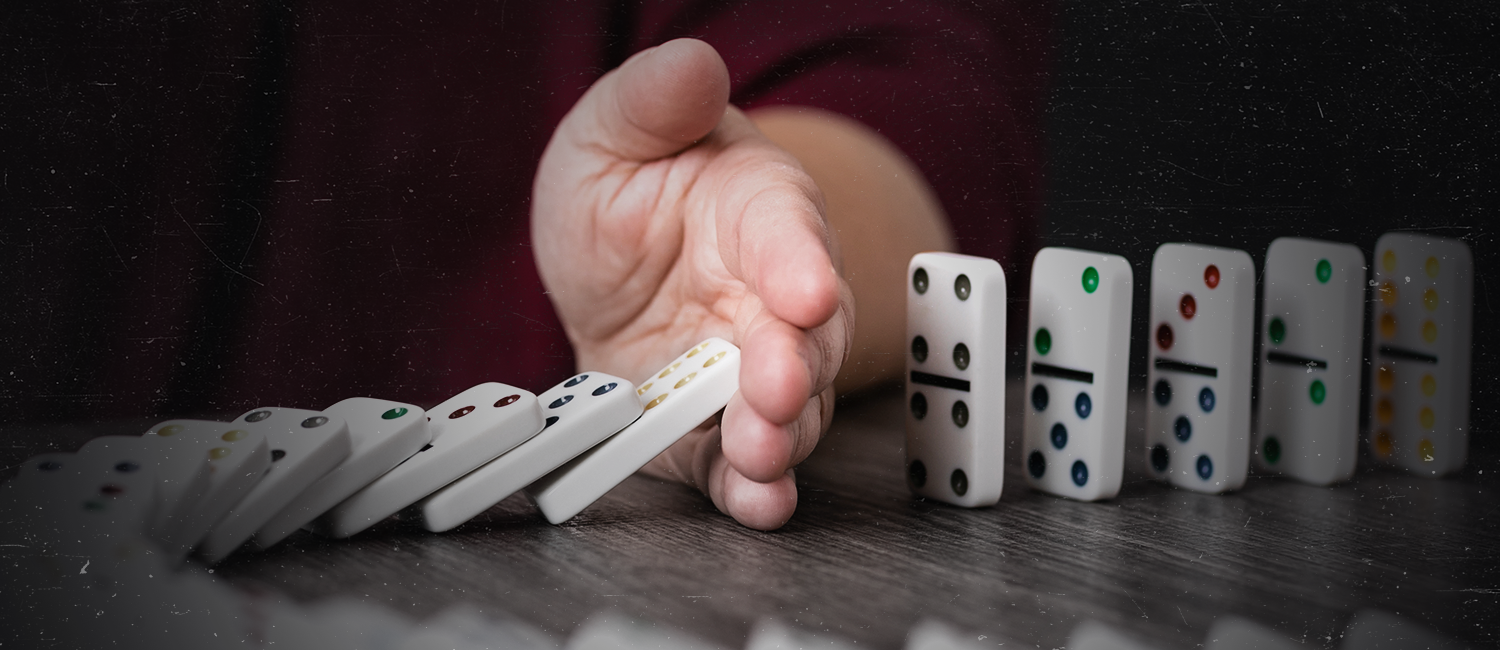 Hand knocking over dominoes