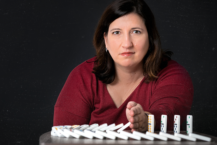 UWM researcher Christine Larson knocking over a row of dominoes