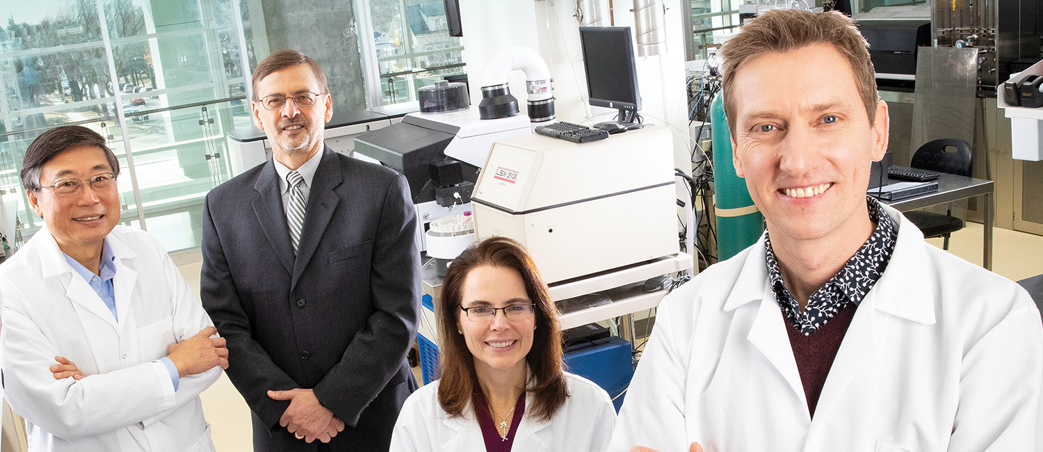 Four people pose for a photo in a research lab
