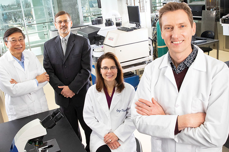 Researchers pose for picture in lab