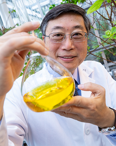 Researcher holds beaker with liquid