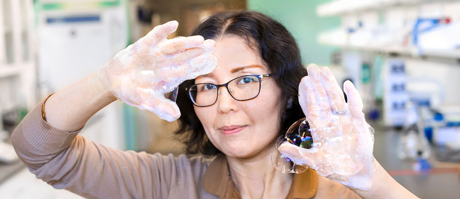 Researcher holds up her soapy hands