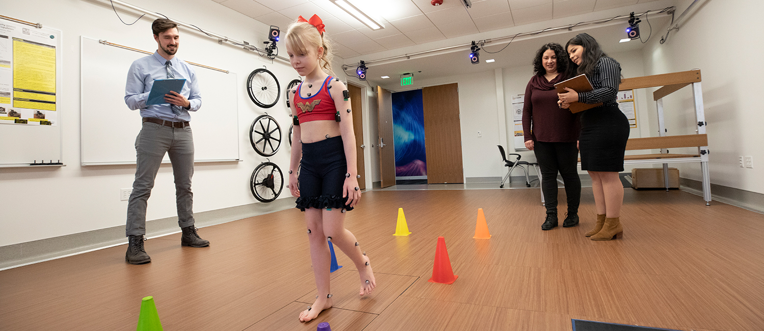 Researchers direct a child through a test at a mobility lab