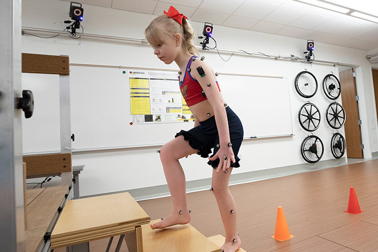 A young girl climbs steps at a mobility lab