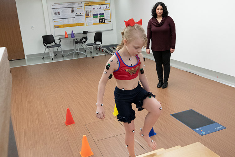 Researcher directs a child through test at a mobility lab