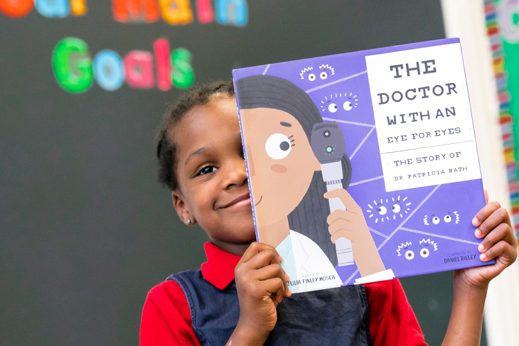 A young girl smiles and holds up a book, covering half of her face