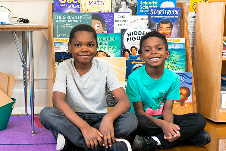 Two young boys smile and sit on a floor in front of a bookcase