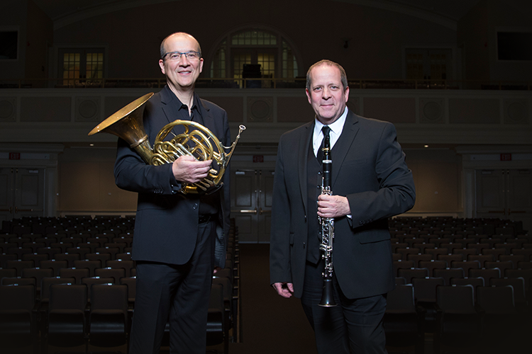 Two UWM professors standing in concert hall holding their musical instruments (French horn and clarinet)