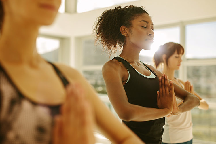 Three women stand in a yoga pose